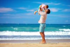 愉快的激动的使用在夏天的父亲和儿子使,享有生活靠岸 免版税库存照片