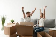 愉快的激动的夫妇一起坐庆祝movin的长沙发 免版税库存图片
