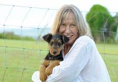 愉快的激动的成熟妇女微笑拥抱的新的小小狗 免版税库存图片