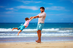 愉快的激动的获得父亲和的儿子在夏天海滩的乐趣,享有生活 免版税库存照片