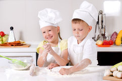 愉快的烹调在厨房里的小男孩和女孩 库存照片