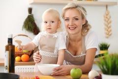 愉快的烹调在厨房里的母亲和小女儿 消费时间全部一起,家庭乐趣概念 免版税库存照片