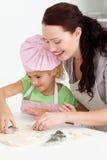 愉快的烹调饼干的母亲和女儿 库存照片
