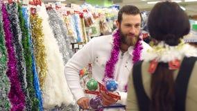 愉快的爱恋的夫妇买的圣诞装饰和礼物圣诞节的 股票视频