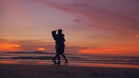 愉快的爱恋的夫妇剪影见面并且使用在日落的海滩在海洋岸 免版税库存照片