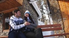 愉快的爱恋的夫妇坐长凳在山的冬天瑞士山中的牧人小屋附近 影视素材