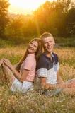 愉快的爱恋的夫妇坐领域 免版税库存照片