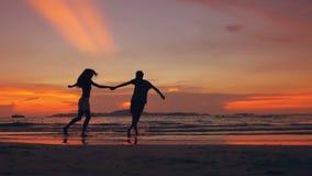 愉快的爱恋的夫妇慢动作剪影见面并且使用在日落的海滩在海洋岸 股票录像