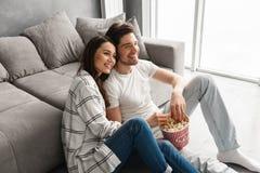 愉快的爱恋的夫妇的图象在家坐地板在沙发附近 库存照片