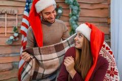 愉快的爱恋的夫妇,人用一条温暖的毯子包括他的女孩 室内 免版税库存照片