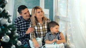 愉快的爱恋的家庭在家坐窗台在圣诞树附近 影视素材