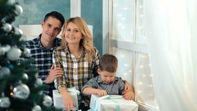 愉快的爱恋的家庭在家坐窗台在圣诞树附近 股票录像