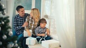 愉快的爱恋的家庭在家坐窗台在圣诞树附近 股票视频