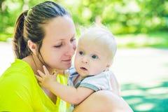 愉快的爱恋的年轻母亲和她的小孩儿子步行的 免版税库存照片