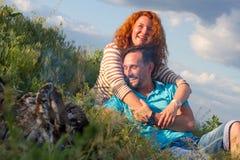 愉快的爱恋的放置由篝火的微笑有吸引力的夫妇拥抱在草和云彩 夫妇爱偶然手表和活跃休息 库存图片
