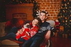 愉快的爱恋的青年人和哈巴狗在圣诞树附近尾随获得乐趣 庆祝新年的微笑的夫妇 定调子 免版税库存图片