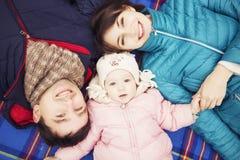 愉快的爱恋的family& x28; 母亲、父亲和一点女儿kid& x29;outd 免版税库存照片