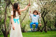 愉快的爱装饰的母亲和小孩儿童儿子获得在摇摆的乐趣在春天或夏天公园 图库摄影
