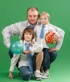 愉快的父亲和两个儿子画象绿色背景的 免版税库存图片