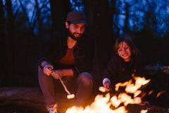 愉快的父亲和他的儿子坐注册在火前面的森林和在小树枝的烤蛋白软糖 免版税库存照片