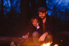 愉快的父亲和他的儿子坐注册在火前面的森林和看它在晚上 免版税库存照片