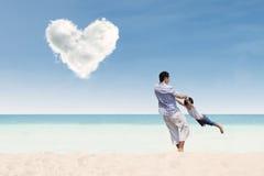 愉快的父亲和儿子充满爱覆盖在海滩 免版税库存图片