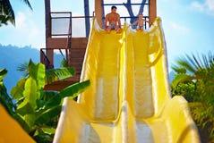 愉快的父亲和儿子准备在热带水色公园滑 免版税库存照片