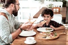 愉快的父亲和儿子吃午餐在吃美味的比萨的自助食堂 免版税库存图片