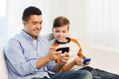 愉快的父亲和儿子有智能手机的在家 库存照片