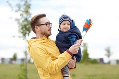 愉快的父亲和儿子有轮转焰火的戏弄户外 免版税图库摄影