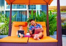 愉快的父亲和儿子繁忙与数字式片剂在度假 免版税库存图片