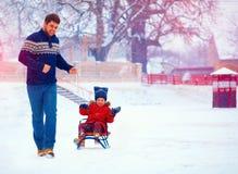 愉快的父亲和儿子获得与爬犁的乐趣在冬天雪下 免版税图库摄影
