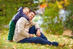 愉快的父亲和儿子获得乐趣在秋天公园 免版税库存图片