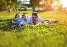 愉快的父亲和儿子获得说谎在草的乐趣在夏天 库存图片