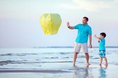 愉快的父亲和儿子飞行一起射击灯笼 免版税库存图片