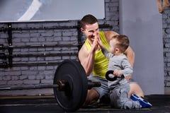 愉快的父亲和儿子画象有杠铃的在十字架适合的健身房对砖墙 库存照片
