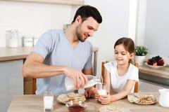 愉快的父亲和女儿吃早餐在厨房,吃可口薄煎饼用果酱,饮料牛奶,享用可口食物 免版税库存照片