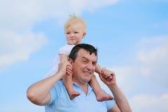 愉快的父亲和女儿户外反对蓝天 库存图片