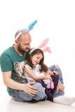 愉快的父亲和女儿有兔宝宝耳朵的 免版税库存图片