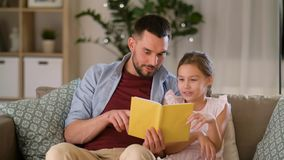 愉快的父亲和女儿阅读书在家 股票视频