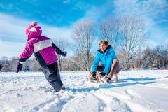 愉快的父亲和孩子与爬犁 图库摄影
