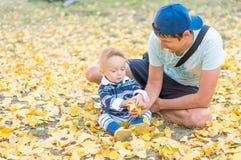 愉快的父亲和小使用与黄色叶子秋天的男婴 库存照片