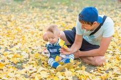 愉快的父亲和小使用与黄色叶子秋天的男婴 免版税库存图片