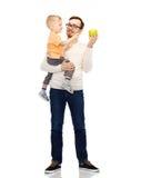 愉快的父亲和小儿子用绿色苹果 库存图片