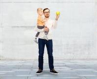 愉快的父亲和小儿子用绿色苹果 免版税库存图片