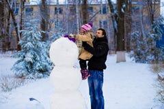 愉快的父亲和小女儿雕刻一个大真正的雪人 免版税库存图片