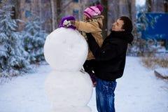 愉快的父亲和小女儿雕刻一个大真正的雪人 库存图片