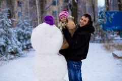 愉快的父亲和小女儿雕刻一个大真正的雪人 库存照片