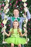 愉快的父亲和小女孩有三叶草的在头在摇摆 免版税库存图片
