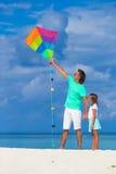 愉快的父亲和小女孩飞行风筝一起 库存图片